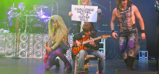 Watch this 11-year old take on a heavy metal band in an epic guitar battle on stage